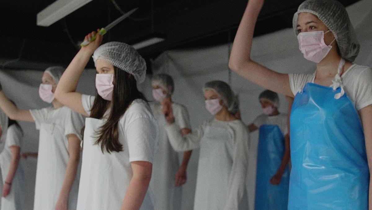 Frauen in Fleischerinnenkluft mit Maske und Fleischermesser.