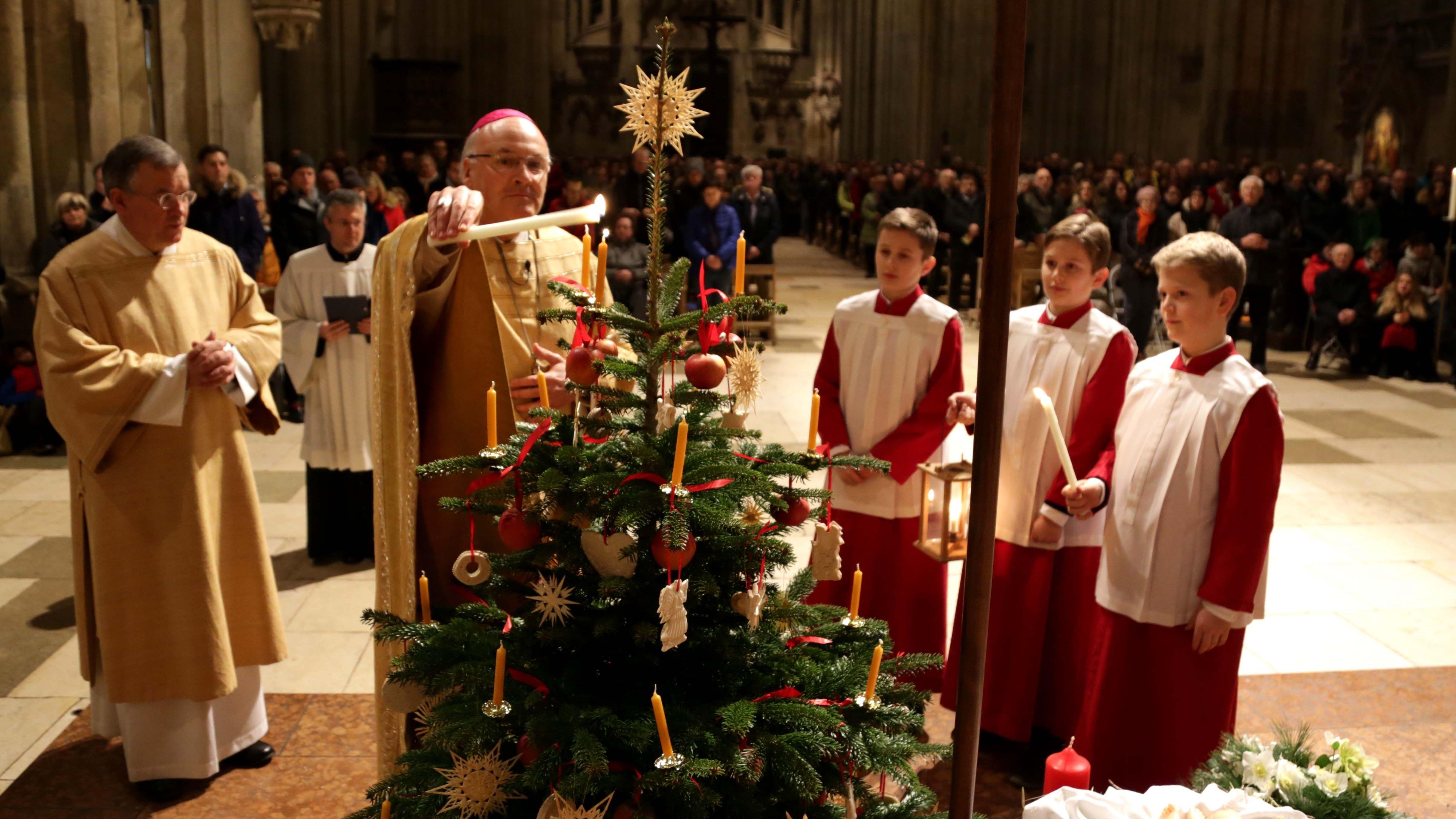 Bischof Voderholzer zündet die Kerzen am Weihnachtsbaum im Regensburger Dom an.