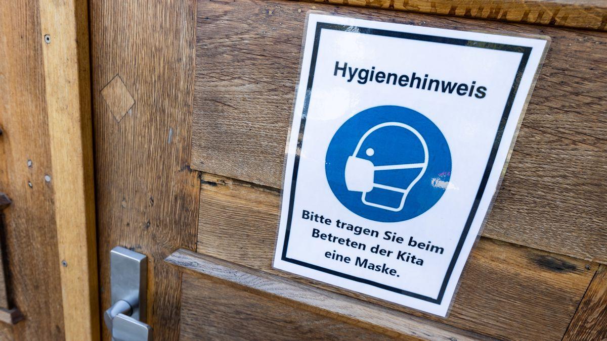 """Schild an der Tür einer Kita: """"Bitte tragen Sie beim Betreten der Kita eine Maske."""" (Symbolbild)"""