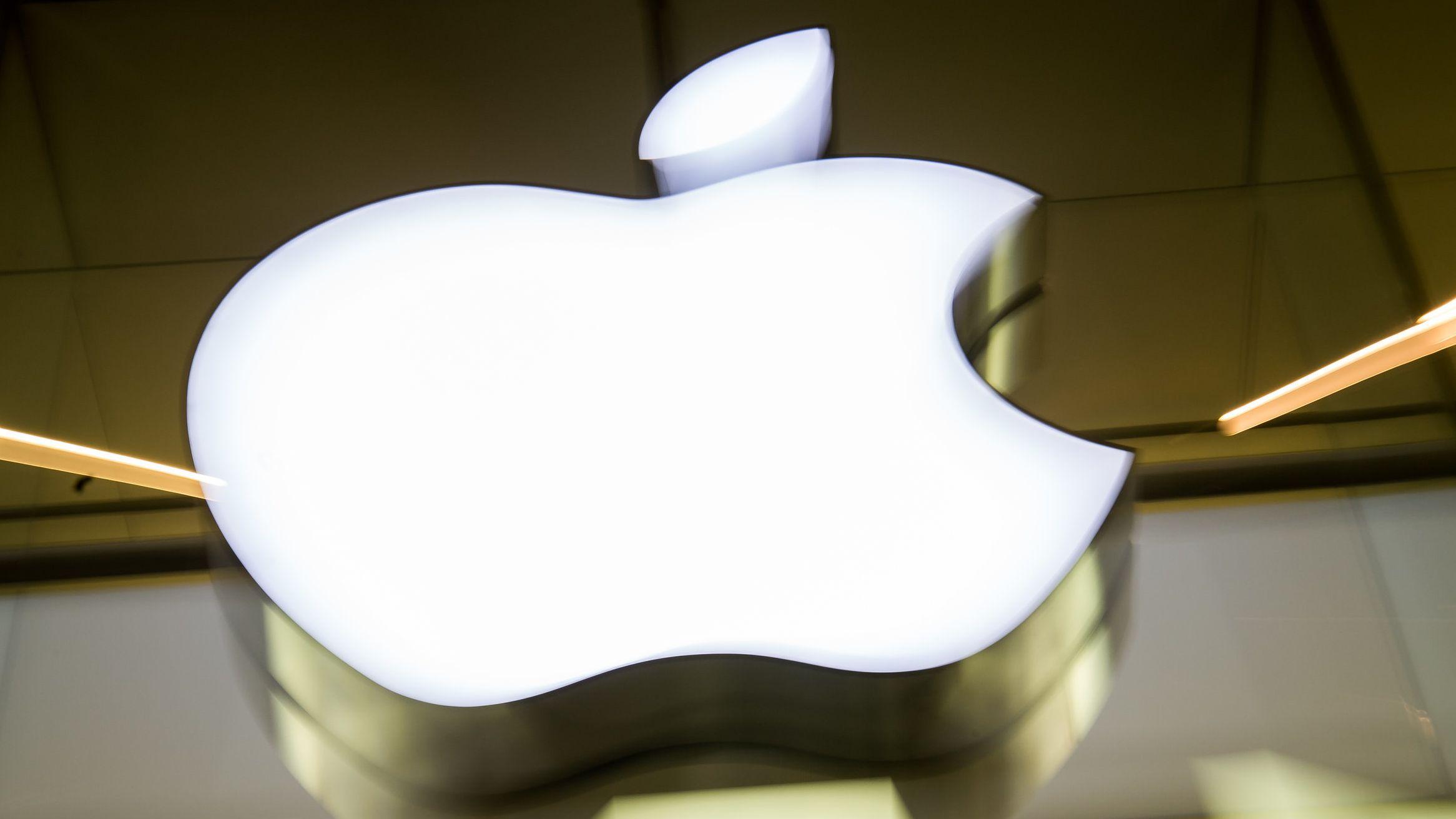 Das Apple-Logo leuchtet an der Fassade eines Münchner Apple Stores.