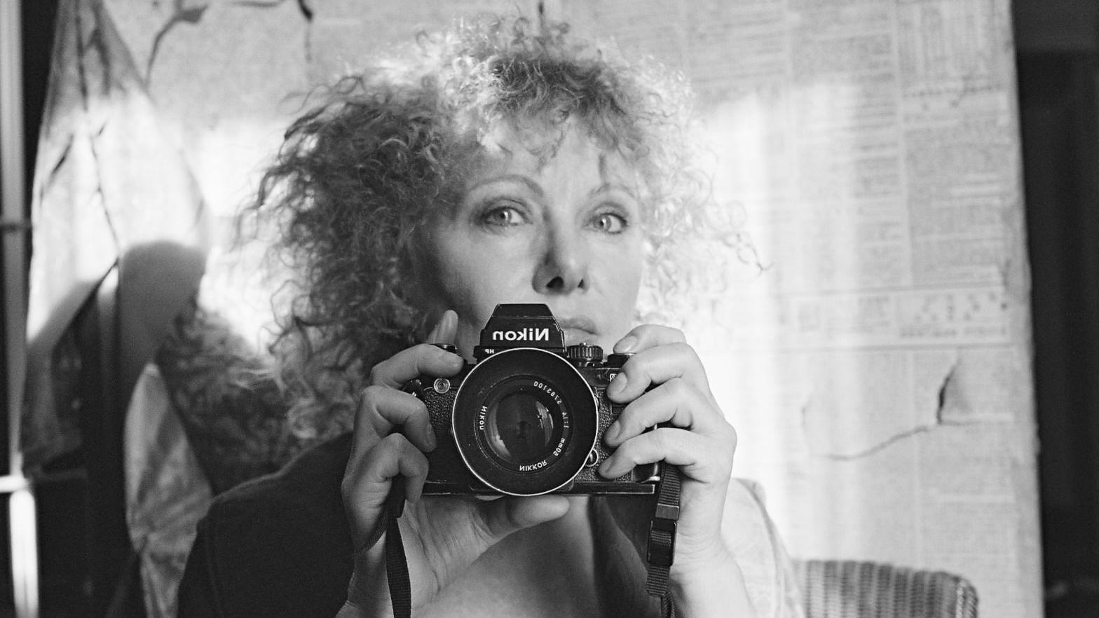 Isolde Ohlbaum, Selbstporträt mit Kamera vor einem hellen Stoffhintergrund (schwarzweiß)