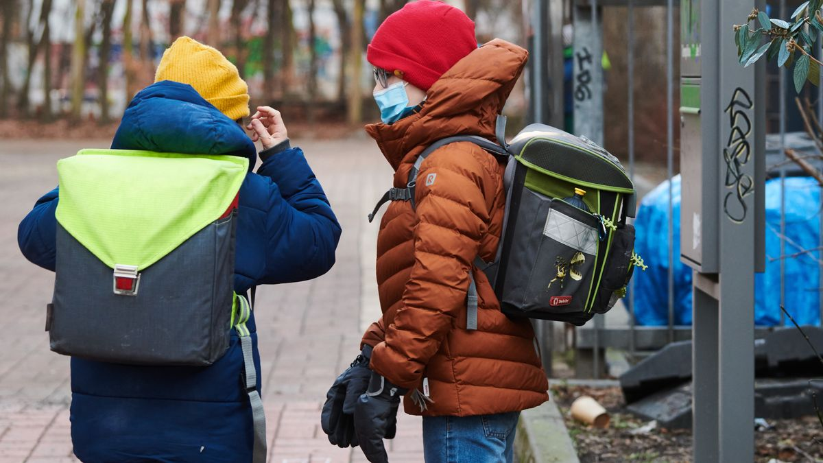 Schulkinder mit Ranzen und Schutzmasken