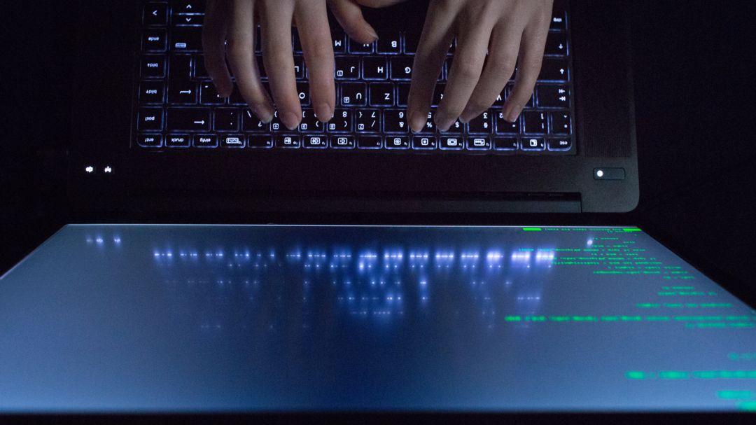 Hände tippen auf einem Laptop mit Programmcode.