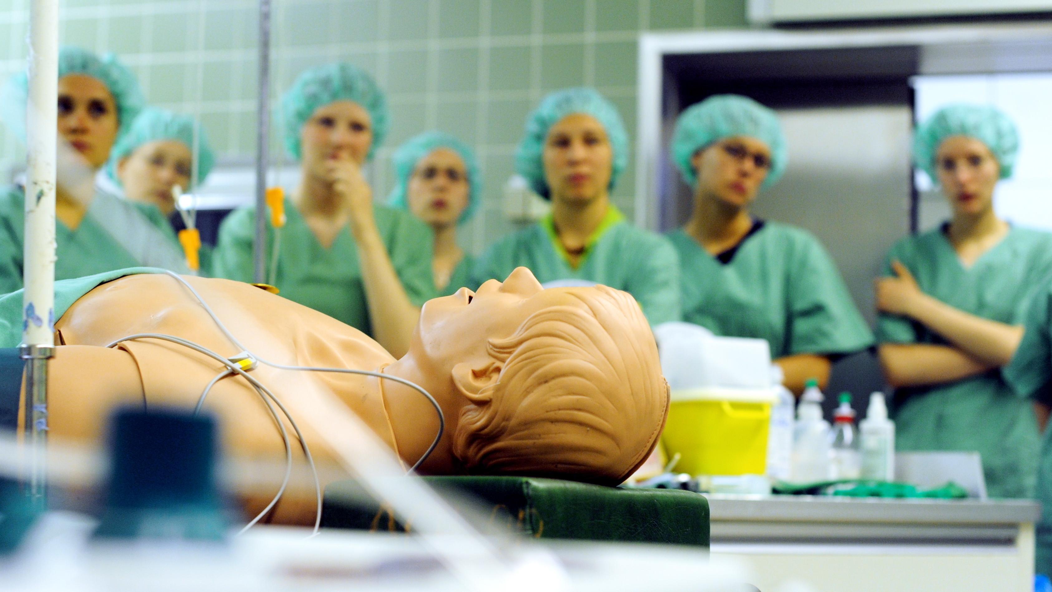 Mehrere Medizinstudenten stehen in einem Operationssaal um eine Puppe herum.