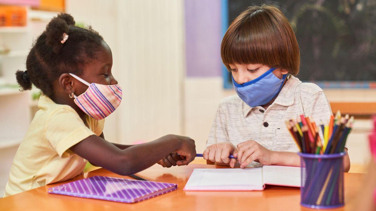 Zwei Kinder sitzen mit Mundschutz wegen Coronavirus-Pandemie an einem Tisch in der Grundschule oder Vorschule