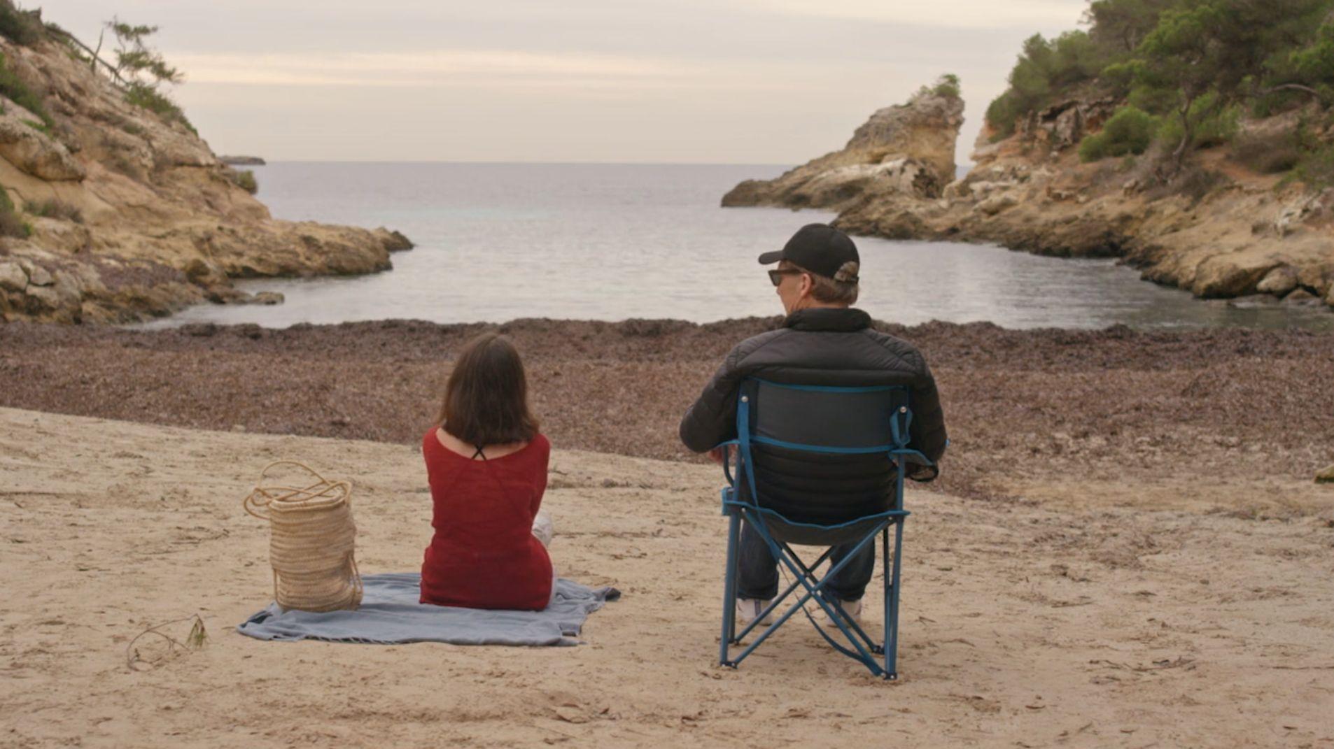 Szenenbild aus dem Film Baumbacher Syndrome - zwei Menschen sitzen nebeneinander am Meer - Sicht von hinten