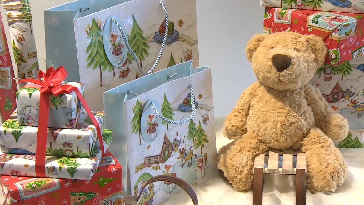 Ein brauner Teddybär sitzt auf einem kleinen Holzschlitten zwischen verpackten Geschenken und Geschenktüten.