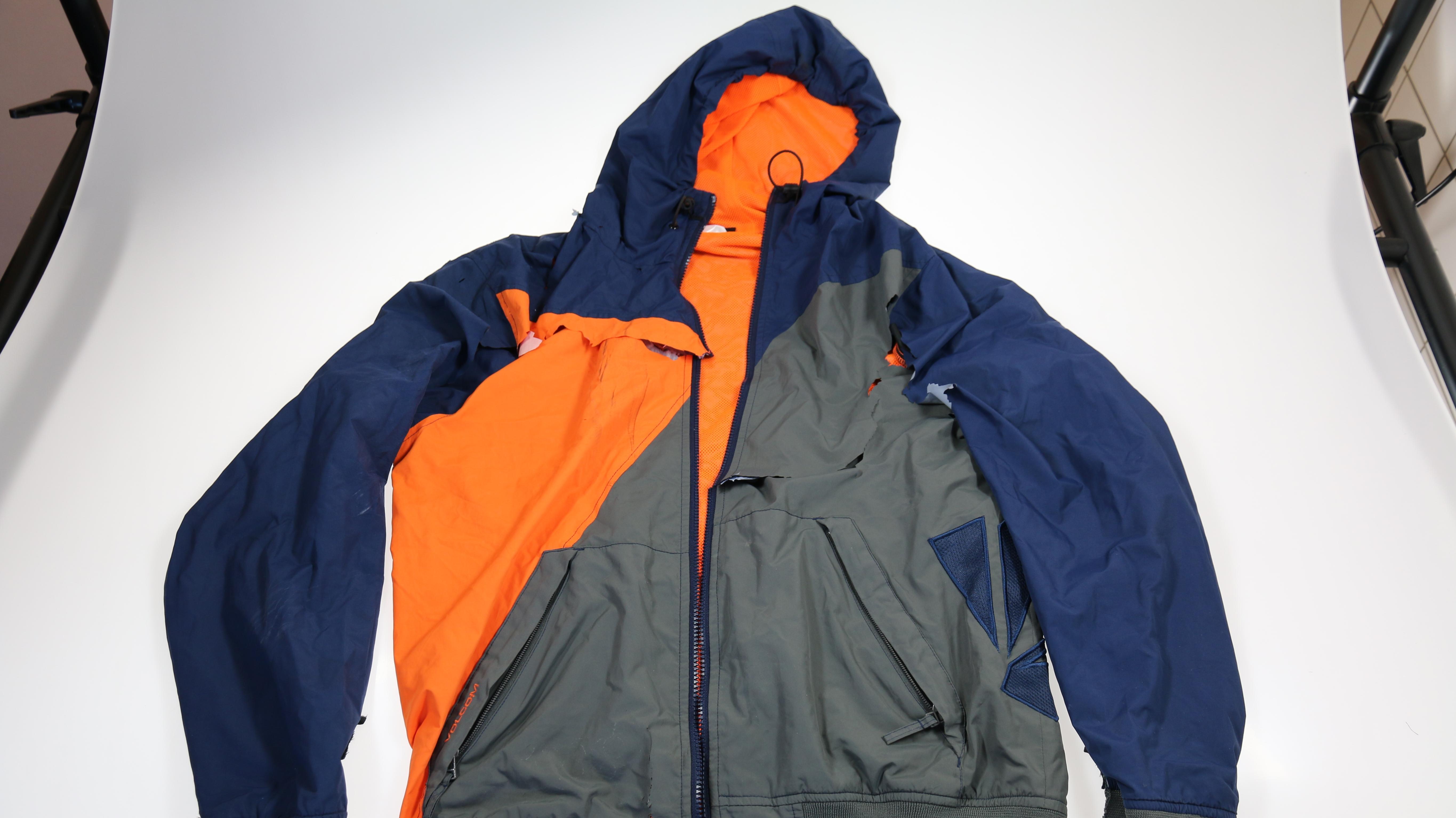 Eine Sportjacke in den Farben blau, grau und orange.