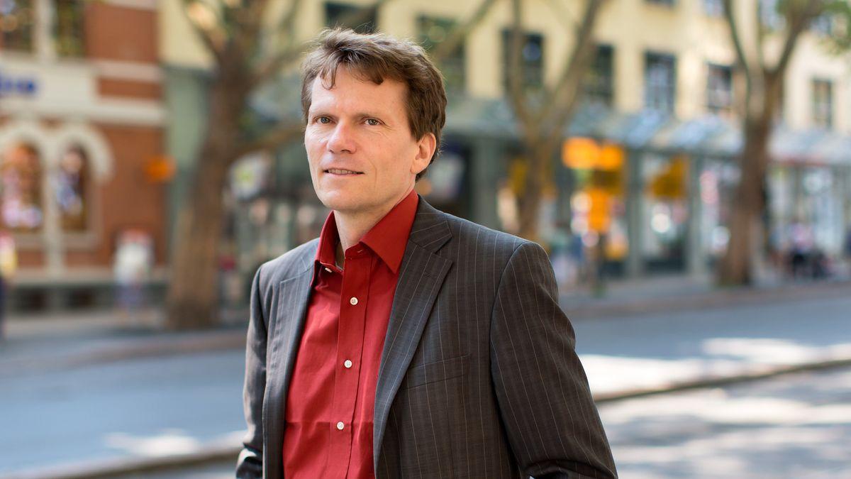 Ein Mann mit rotem Hemd und grauem Sakko mit hellen Nadelstreifen, im Hintergrund unscharf eine Ladenstraße