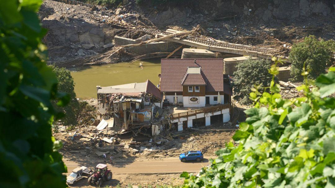 Rheinland-Pfalz, Marienthal: Ein Haus ist nach dem Hochwasser vollkommen aufgerissen, dahinter ist eine zerstörte Brücke zu sehen.