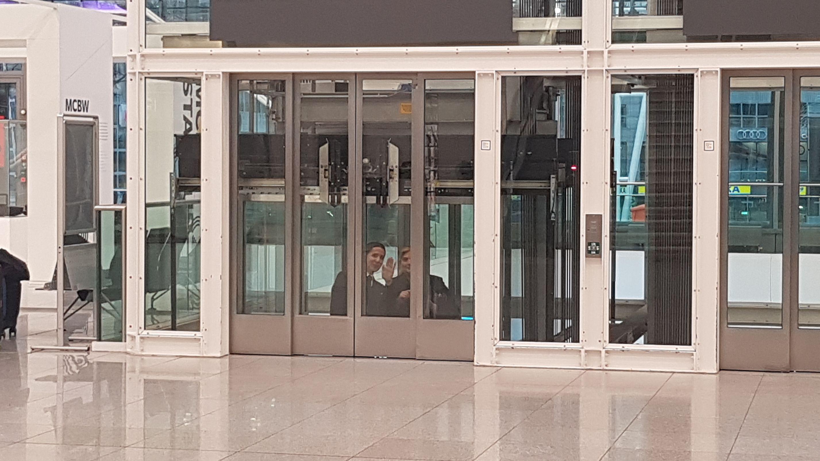Am Münchner Flughafen ist teilweise der Strom ausgefallen. Diese beiden Fahrgäste stecken im Aufzug fest - aber sie nehmen es mit Humor.