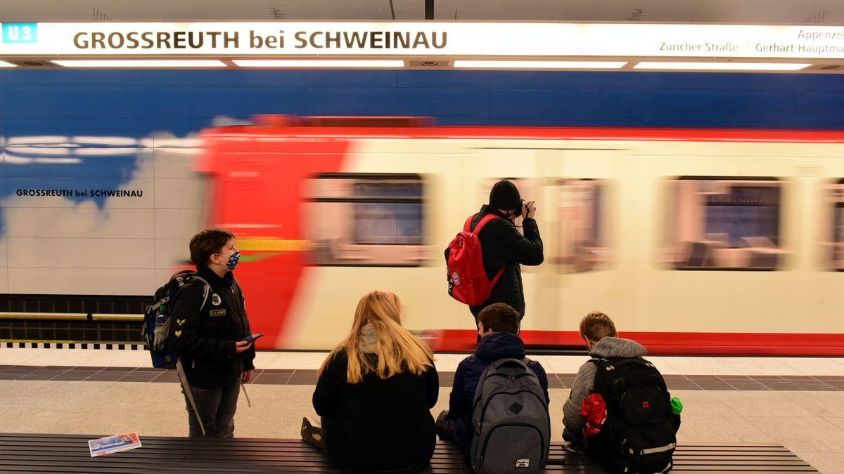 Wartende am Bahnsteig der neuen Endstation der U3 in Nürnberg Großreuth - im Hintergrund fährt ein U-Bahn-Zug