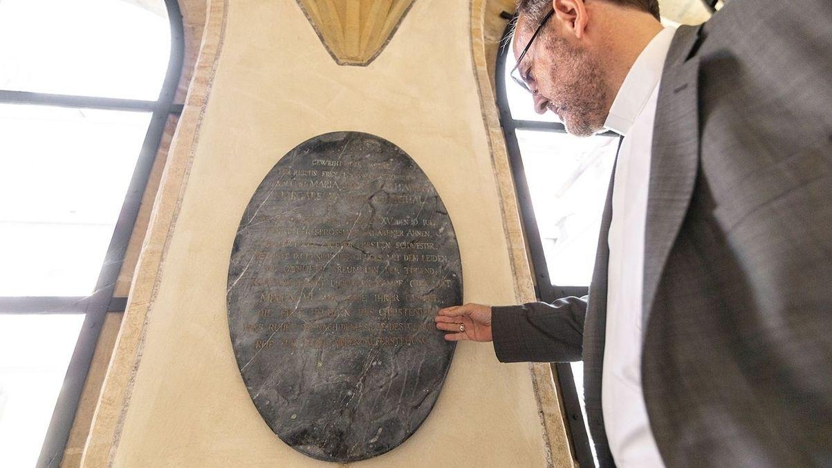 Mann im Anzug deutet auf Grabplatte von Sophie Marie von Erthal