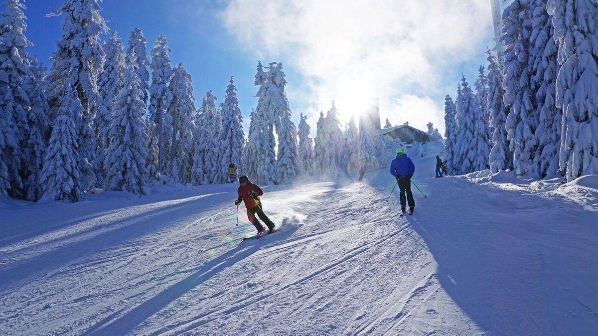 Skifahrer fahren einen verschneiten Hang hinunter.
