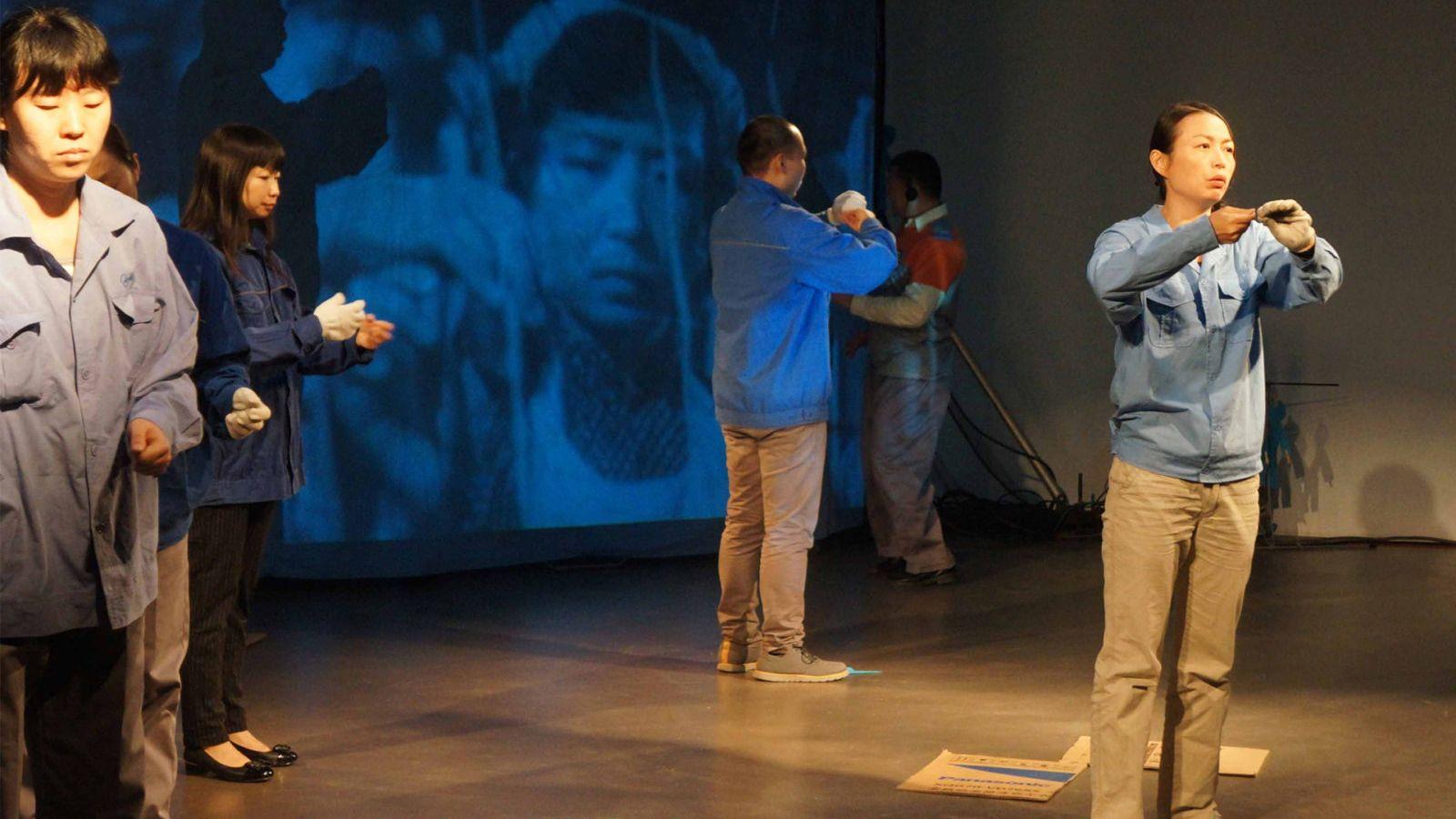 """Fünf Frauen und Männer stehen in einem Raum und verrichten mit trauriger Mine die gleichen Handbwewgungen: Aufführung des Tücks """"World Factory"""" von Zhao Chuang"""