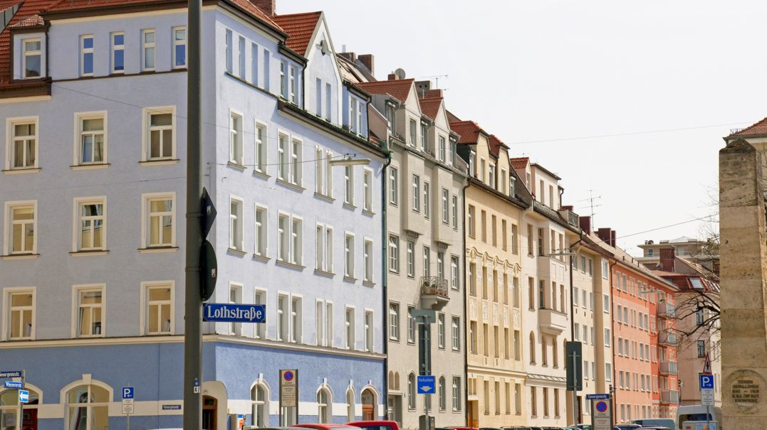 Häuserfassade entlang der Lothstraße in München, Häuser in hellblau, beige, gelb und orange.