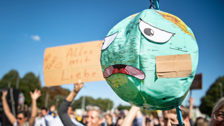 Demonstranten halten einen Luftballon mit Globusaufdruck hoch, der mit einem Pflaster und unglücklichen Gesichtszügen beklebt ist