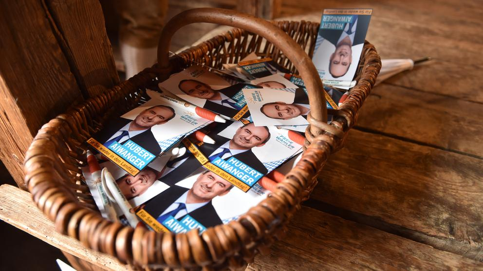 Flyer mit dem Bild von Freie-Wähler-Spitzenkandidat Hubert Aiwanger liegen beim politischen Frühschoppen Gillamoos in einem Korb. | Bild:Lino Mirgeler/dpa