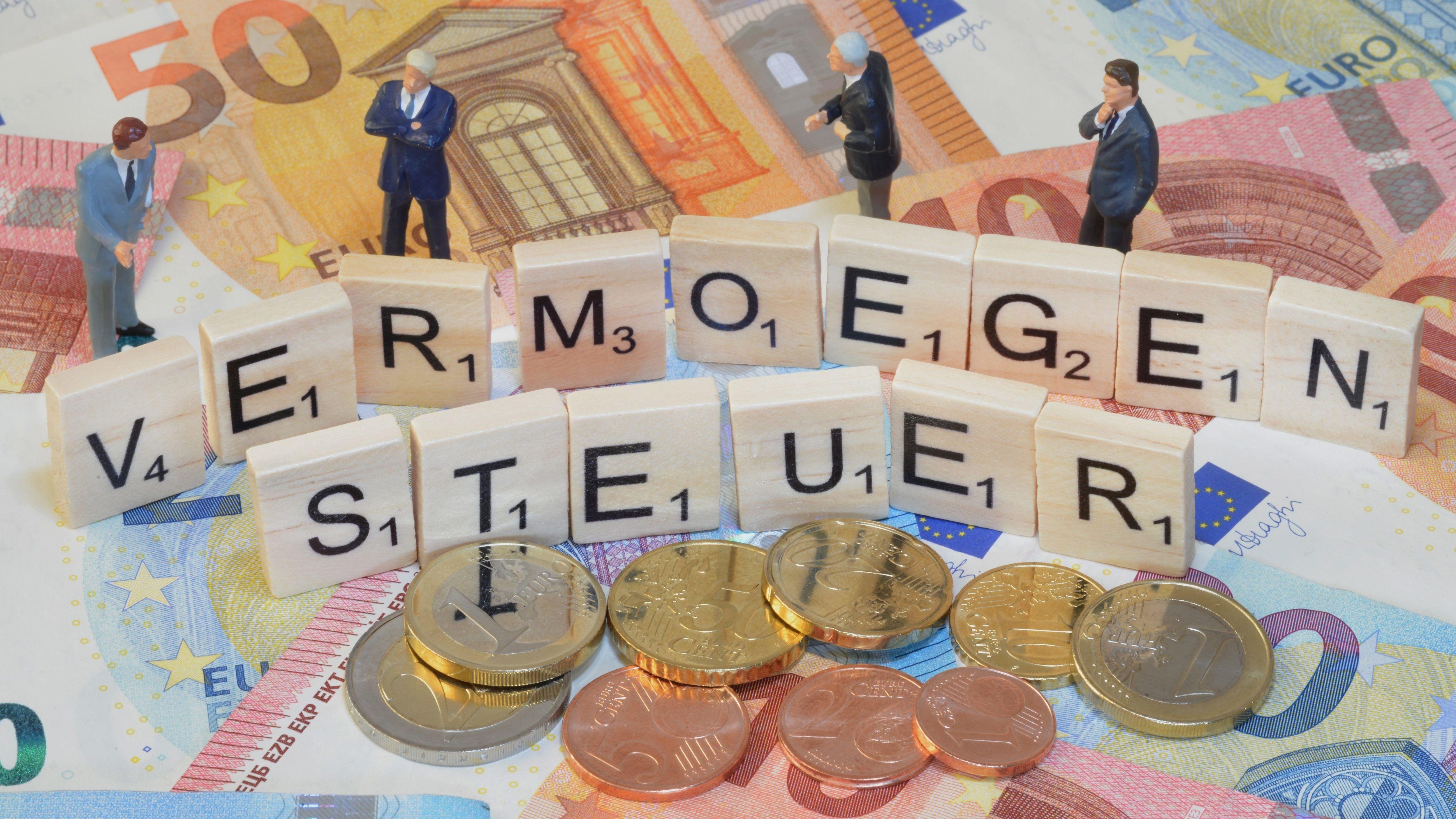 Spielzeugmännchen stehen auf Geldscheinen zusammen mit dem Wort Vermögensteuer aus Scrabble-Buchstaben.