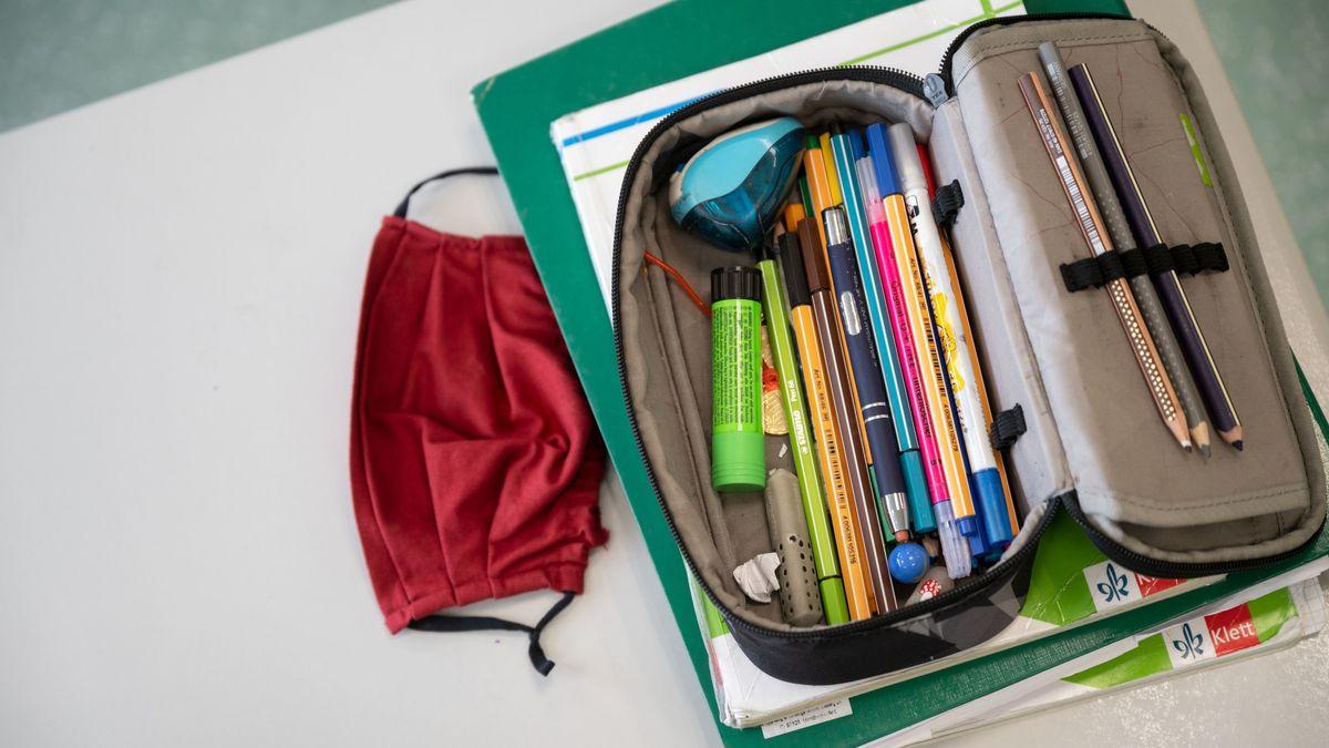 Hefte, Schulbücher, ein Mäppchen mit Stiften und eine rote Maske liegen auf einem Tisch