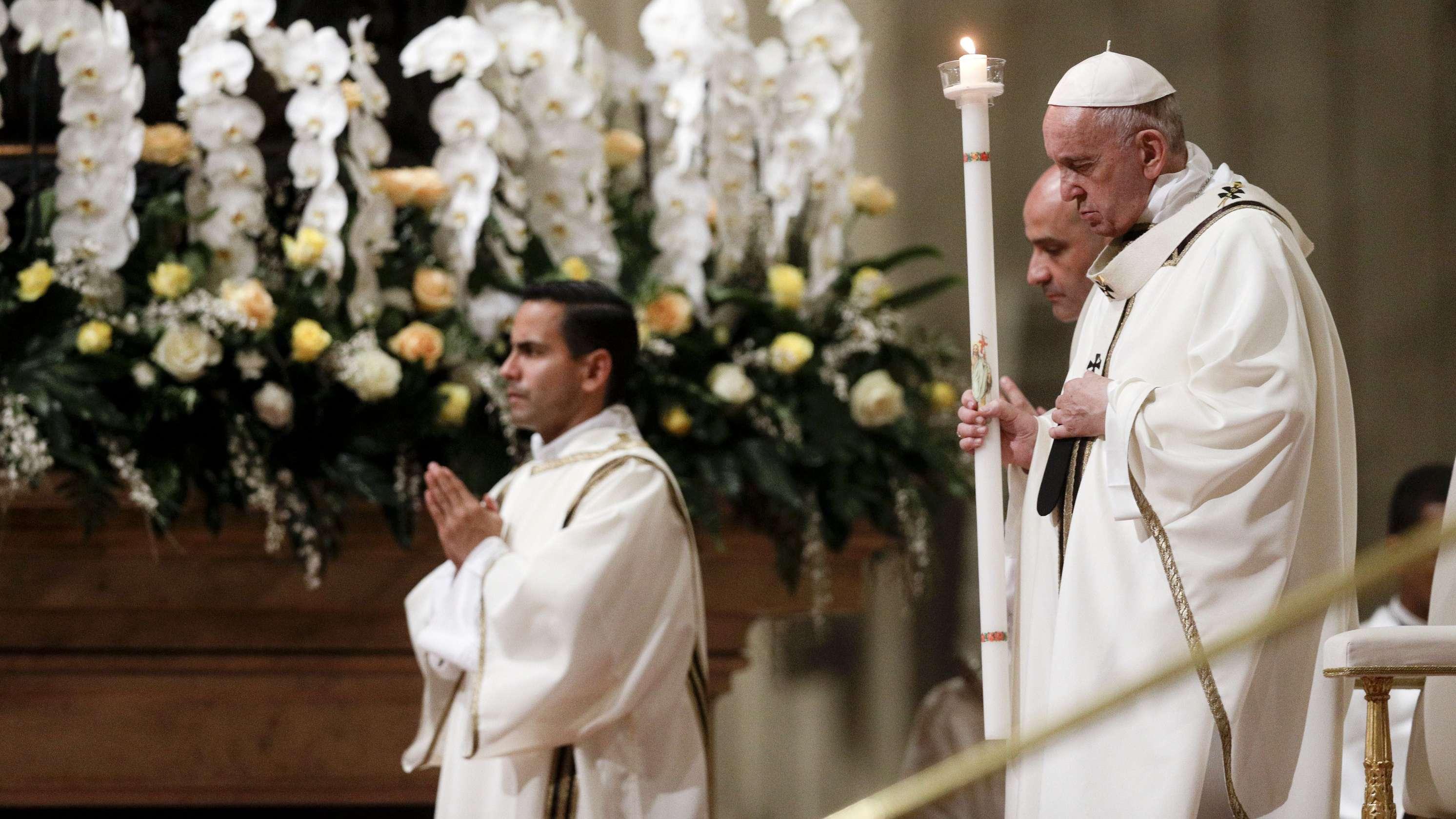 Papst Franziskus (r) hält eine Kerze, während er der feierlichen Osternacht im Petersdom vorsitzt