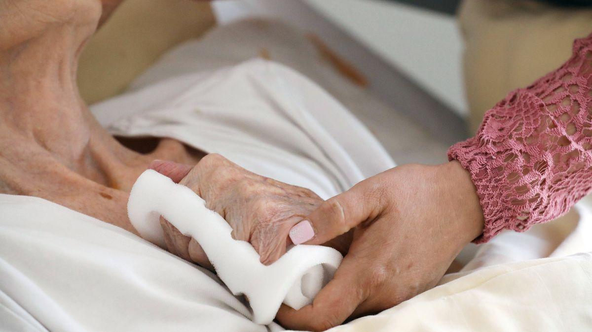 Eine Pflegeschwester hält die Hand einer Heimbewohnerin.