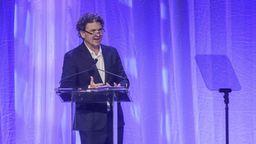 Vor einem blau-violett glänzenden Vorhang steht ein mittelalter Mann mit krausem Haar und Brille an einem Rednerpult: Dave Eggers | Bild:Brian Bohannon AP Invision
