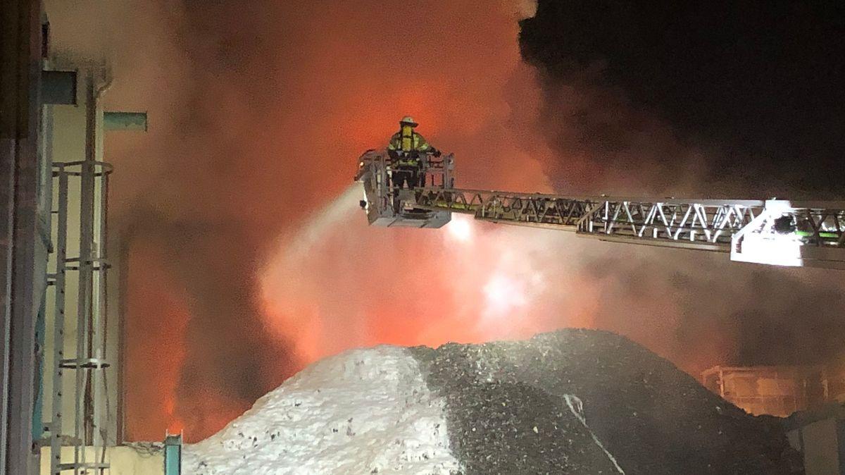 Ein Feuerwehrmann auf einem ausziehbaren Schwenkarm versucht das Feuer auf dem Recyclinghof zu löschen