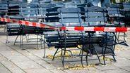 Tische und Stühle stehen vor einem Restaurant, das im Teil-Lockdown geschlossen hat. | Bild: Hauke-Christian Dittrich/dpa