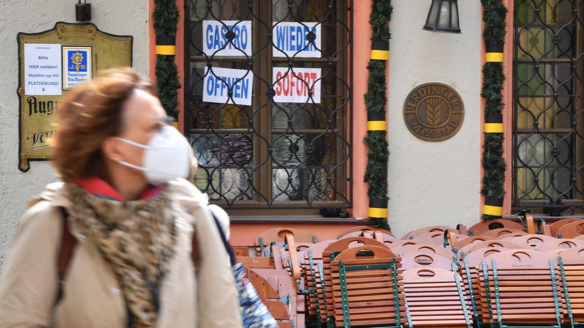 Frau mit Maske vor einem geschlossenen Restaurant