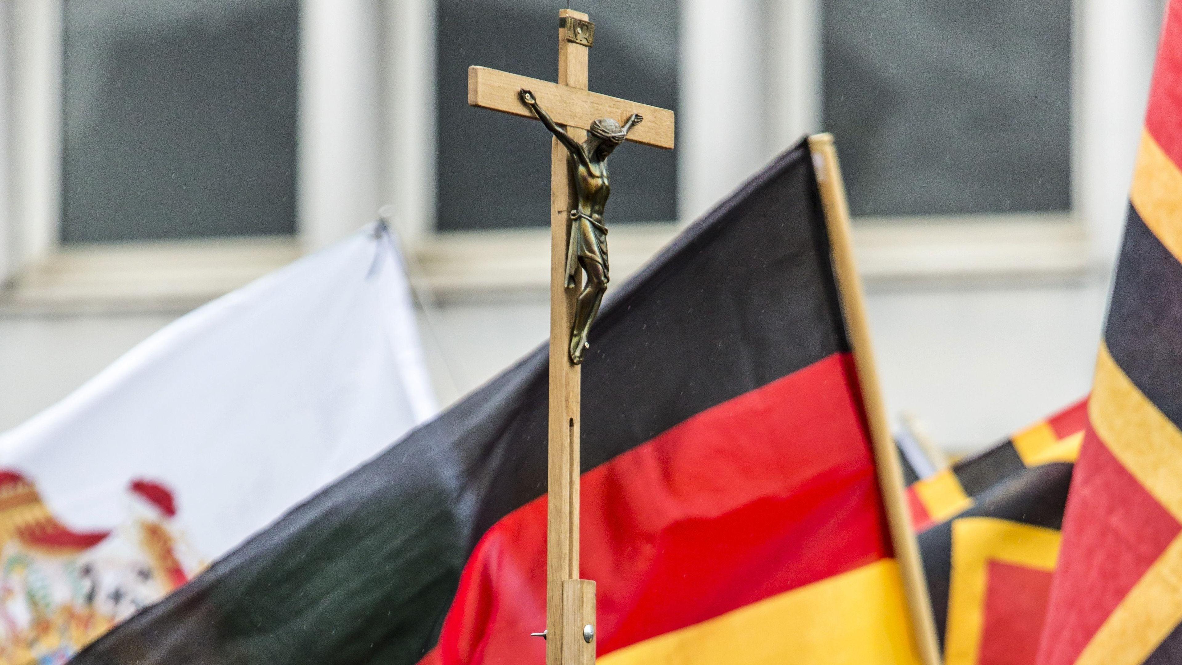 Auf einer PEGIDA-Demonstration wird neben Deutschlandfahnen auch ein Kreuz mitgetragen. (Symbolfoto)