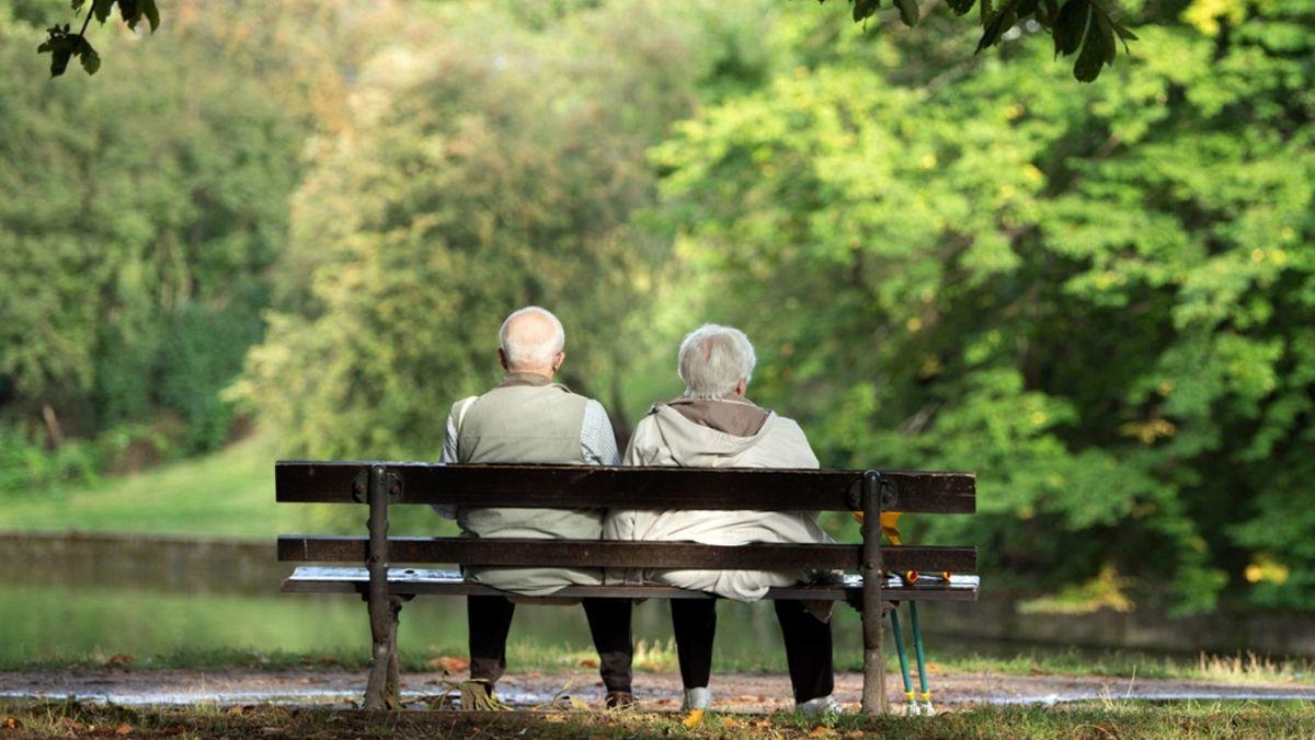 Ein Rentner-Ehepaar sitzt auf einer Bank