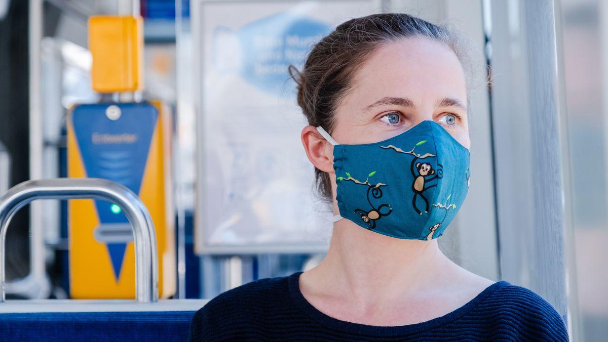 Frau mit Gesichtsmaske sitzt in Leipzig in der Straßenbahn.