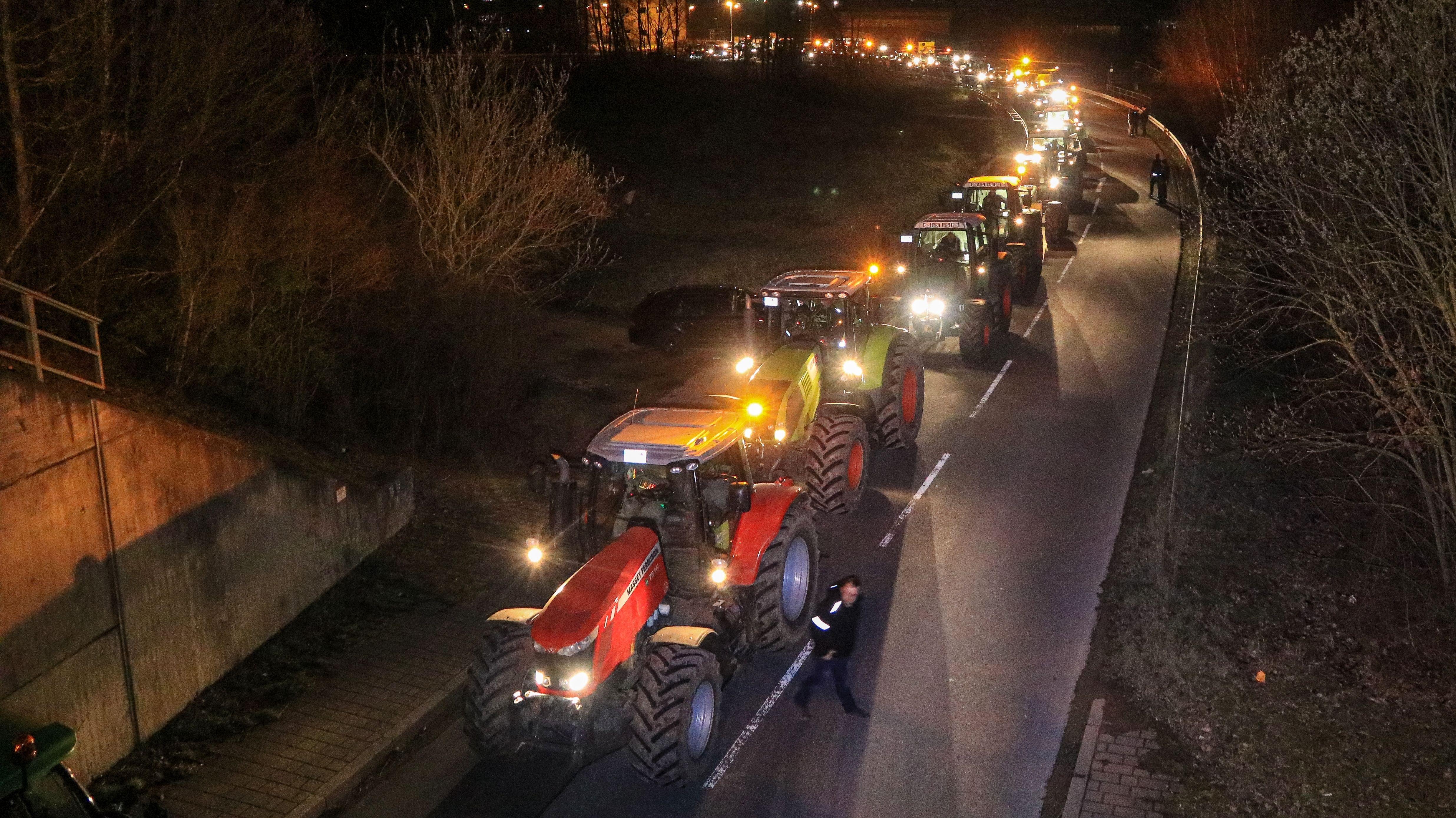 Landwirte stehen von ihren Traktoren, die die Zufahrt zum Zentrallager von Rewe in Buttenheim versperren.