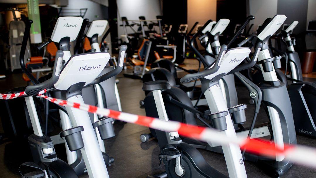 Ein rot-weißes Flatterband ist an Fahrradtrainern befestigt, die in einem Fitnessstudio stehen.
