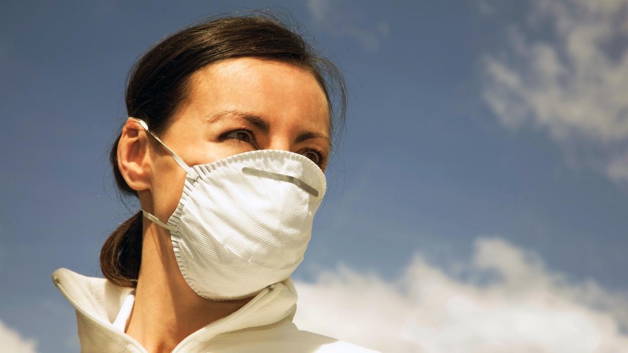 Frau mit einer Atemschutzmaske steht im Freien.