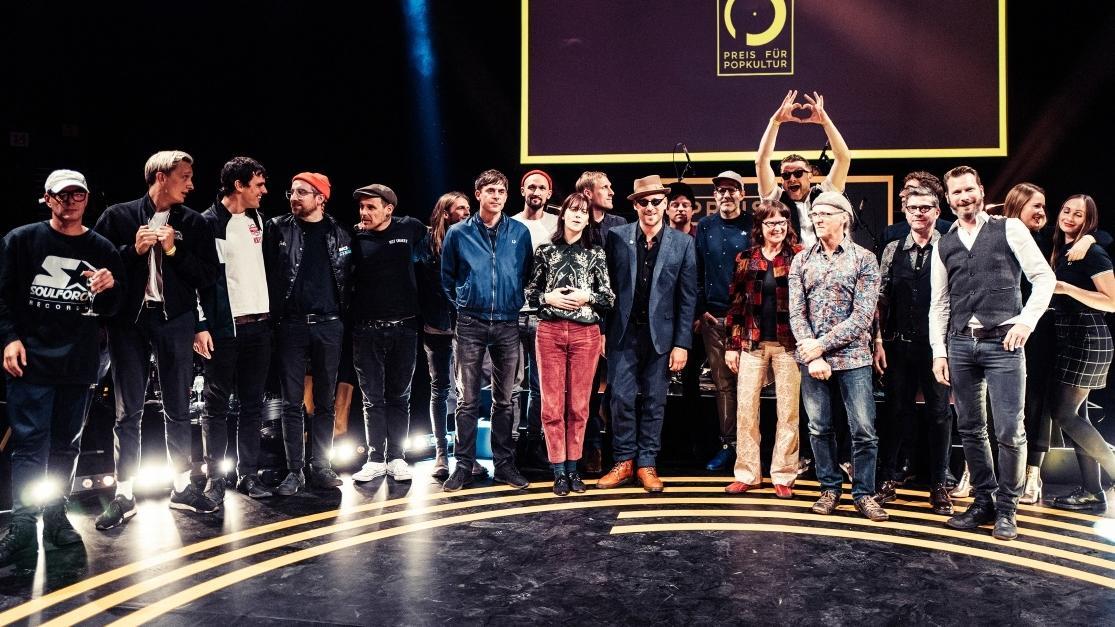 Gruppenbild zum Preis für Popkultur 2018: Gewinnerinnen und Gewinner stehen im Halbkreis auf der Bühne