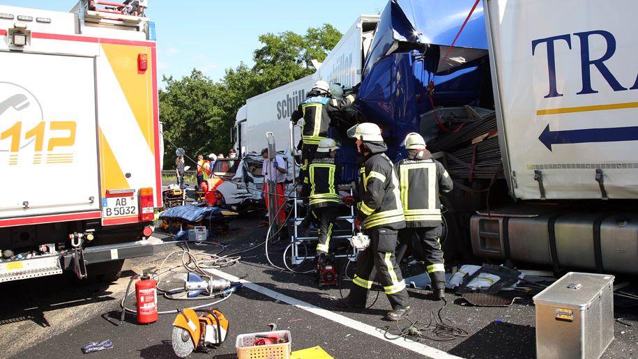 Feuerwehrmänner und ineinander verkeilte LKW