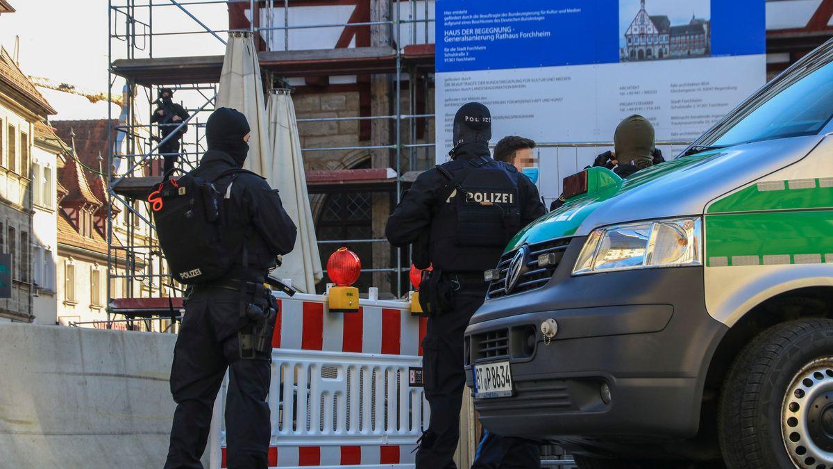 Polizisten in Kampfanzug stehen zwischen einem Polizeibus und einer Baustellenabsperrung, im Hintergrund steht ein Beamter auf einem Baugerüst.