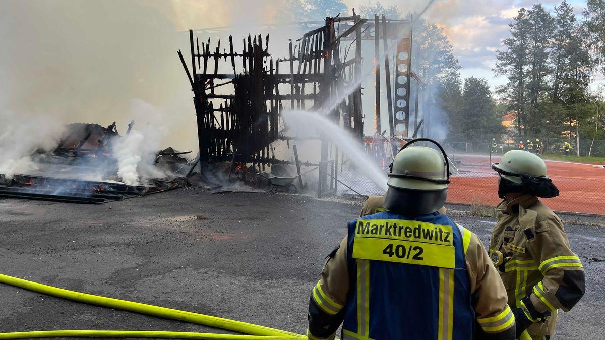 Einsatzkräfte der Feuerwehr löschen mit Wasser die Ruine der abgebrannten Tennishalle, die stark qualmt.