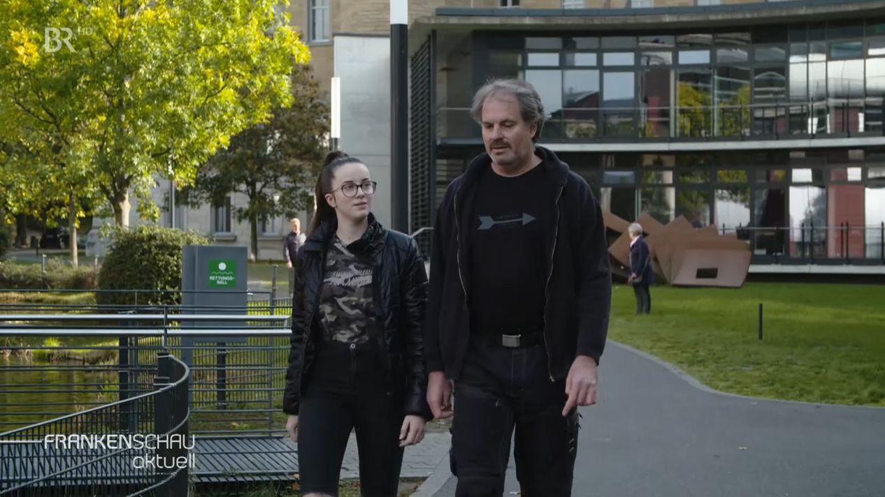 Die Schwester und der Vater einer getöteten Frau laufen einen Weg entlang.