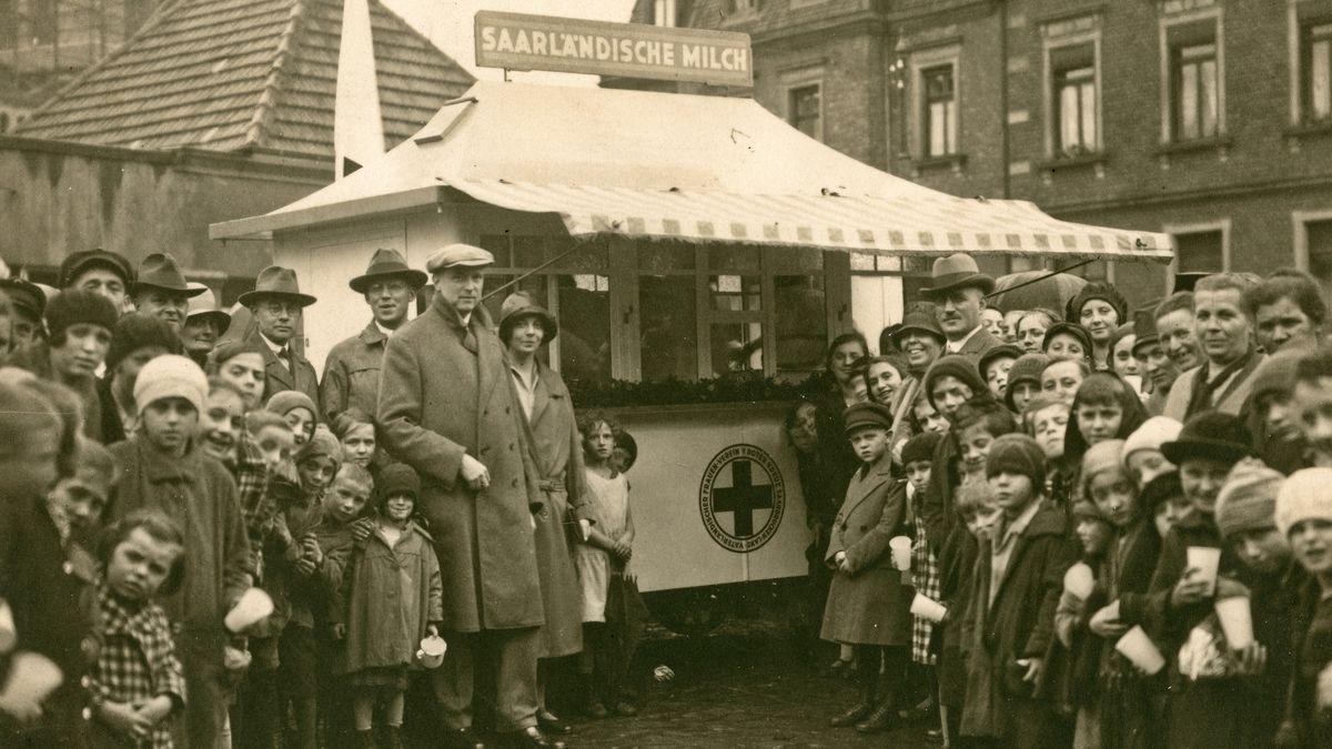 Ausgabe von Milch an Bedürftige durch das DRK: Stand des DRK in Saarbrücken, umringt von Bevölkerung in den 20er Jahren.