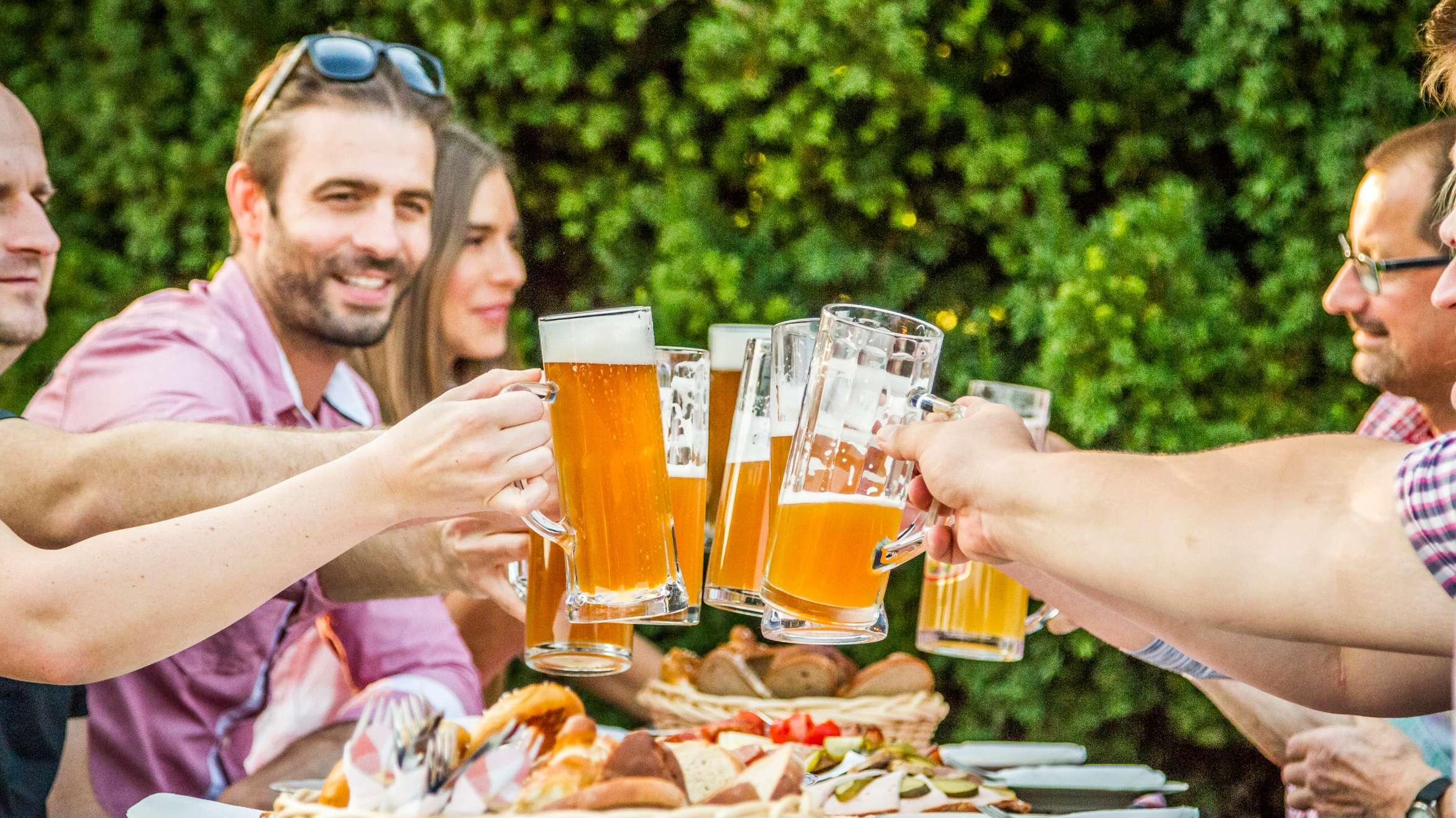 Eine Gruppe von Menschen sitzt im Biergarten und stößt mit Zoiglbier an
