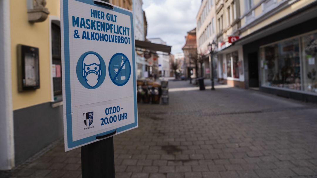 Ein Schild weist in der leeren Fußgängerzone Kulmbachs auf die Maskenpflicht hin.