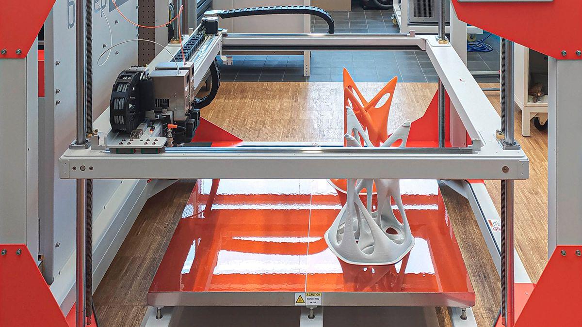 Ein großer rot-silberner 3D-Drucker.