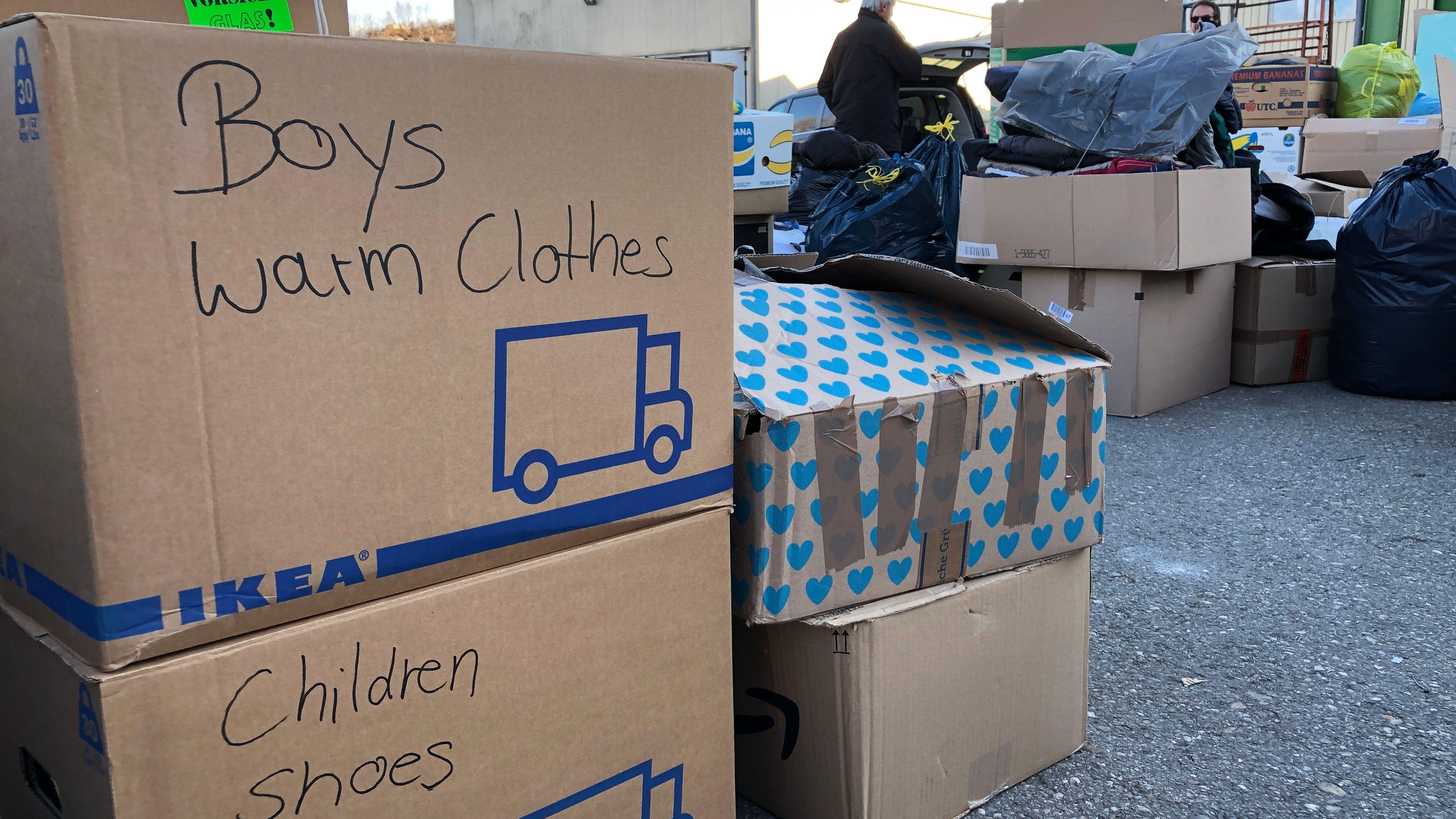 Kartons mit Kinderkleidung und -schuhen stehen auf dem Boden