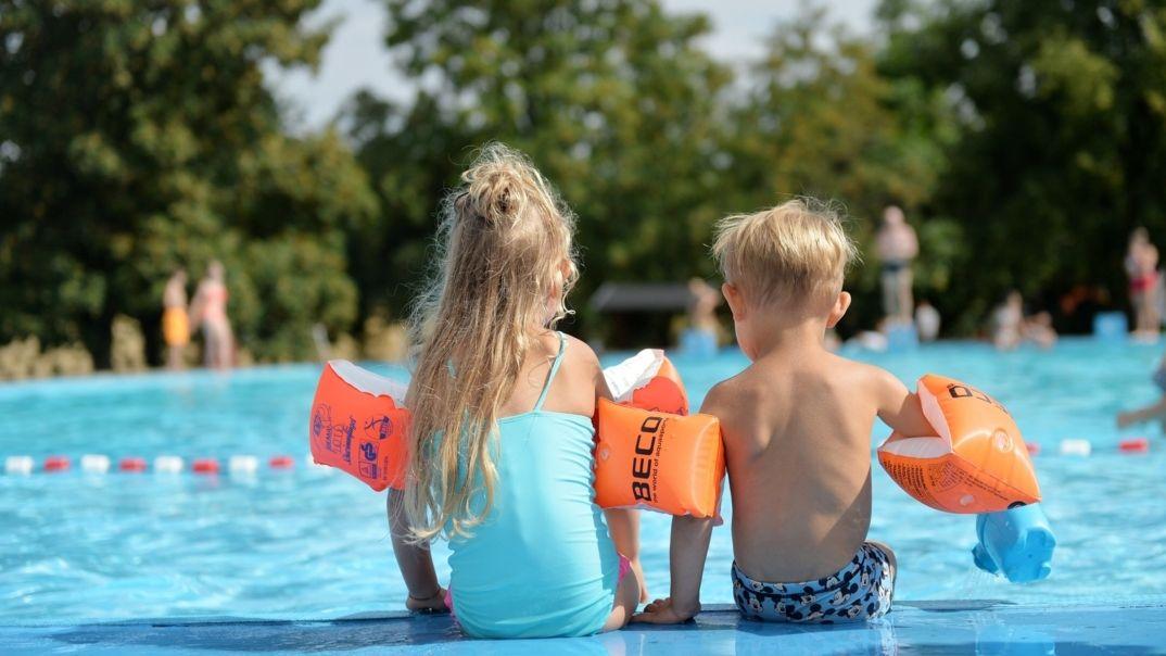 Symbolbild /zwei Kinder mit Schwimmflügeln sitzen am Rand eines Beckens im Freibad
