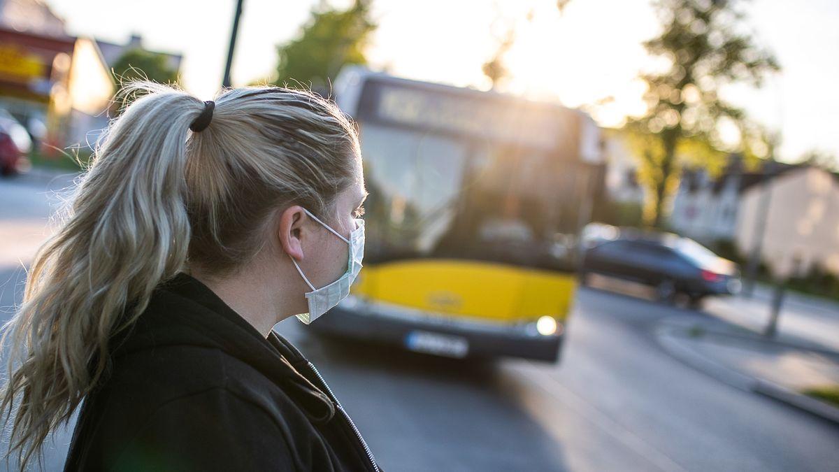 Eine Frau steht mit Mundschutz an einer Bushaltestelle und wartet auf einen Bus.