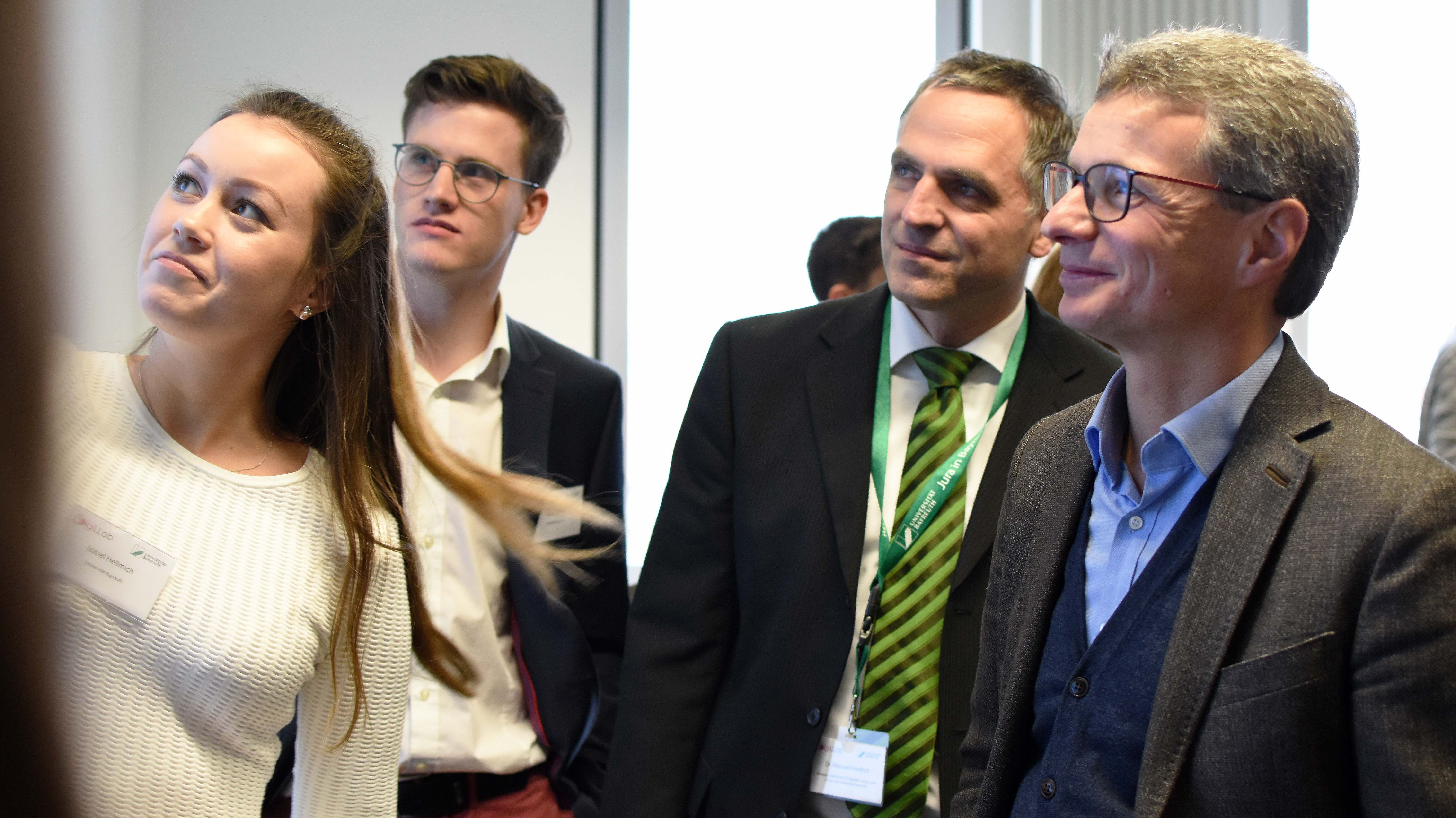 Wissenschaftsminister Bernd Sibler (CSU) blickt mit anderen Gästen bei der Eröffnung des DigiLLab an der Uni Bayreuth auf einen Monitor an der Wand.