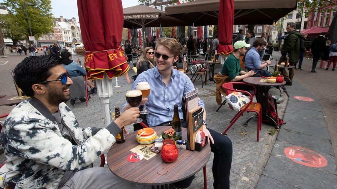 Utrecht: Männer stoßen auf einer Café-Terrasse an. Die Niederlande haben einige Einschränkungen zur Eindämmung der Corona-Pandemie gelockert.
